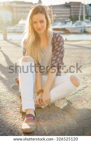 Lifestyle portrait of a young attractive woman sitting on a skateboard in afternoon sun - stock photo