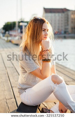 Lifestyle portrait of a young attractive woman sitting on a skateboard outdoors - stock photo