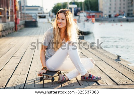 Lifestyle portrait of a young attractive woman sitting on skateboard outdoors