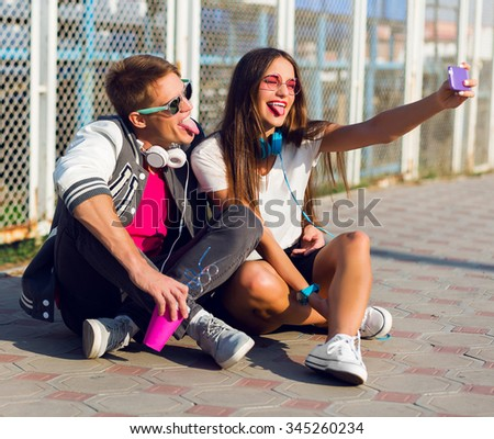 Lifestyle portrait of  amazing young couple in love makes emotional  selfie , grimace, shows tongue. Wearing bright spring modern clothes, sportive urban style .