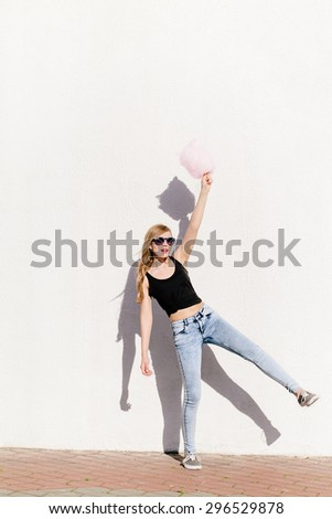 Lifestyle portrait of beautiful blonde girl having and holding cotton candy in hand. Wearing sunglasses, red lips. Casual style, outdoors - stock photo