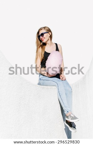 lifestyle portrait of beautiful smiling girl sitting outside with pink cotton candy. Wearing sunglasses. Red lips. White background, not isolated. - stock photo