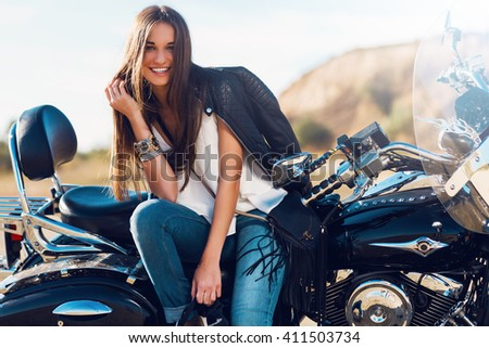 Lifestyle portrait of  cheerful stylish  woman sitting on motorbike on the beach and  smiling ,  have perfect fit slim tamed body and long hairs. Outdoor lifestyle portrait. - stock photo