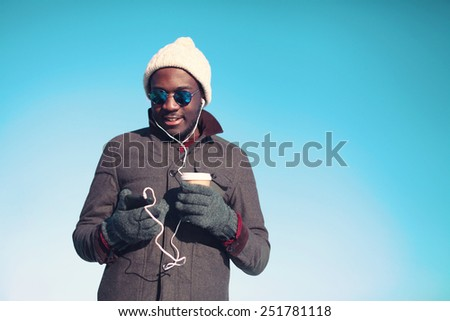 Lifestyle portrait of free young african man enjoying listening music on smartphone with a paper cup of coffee against blue sky in sunny clear day - stock photo