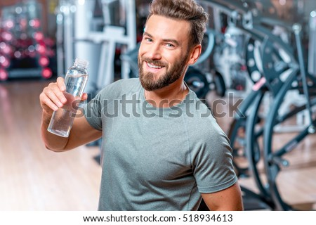 Lifestyle portrait handsome muscular man drinking stock photo lifestyle portrait of handsome muscular man drinking water in the gym sciox Gallery