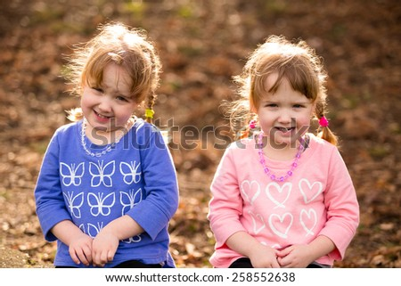 Lifestyle portrait of identical twin sisters at a park interacting and having fun together. - stock photo