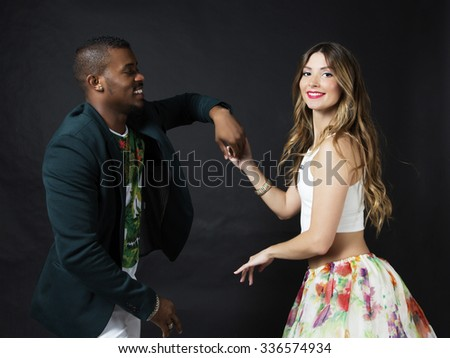 Lifestyle portrait of of happy smiling dance couple, holding hands. Wearing bright clothes with floral print. Smiling and dancing latino. The girl's make up arrow, red lips and curly blonde hair - stock photo