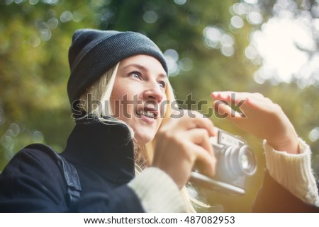 Lifestyle portrait of pretty young woman Making pictures with retro camera. Smiling hipster girl having fun in outdoor park wearing black popular coat and leather  backpack.