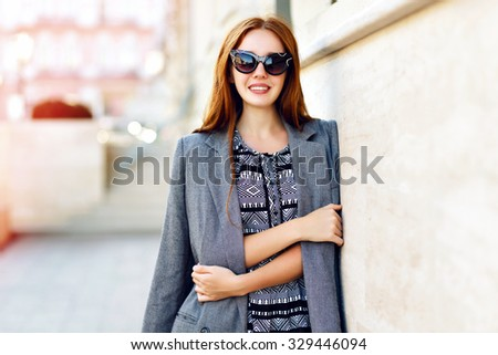 Lifestyle portrait of stunning hipster girl, wearing elegant glamour jacket dress and vintage sunglasses, toned warm colors, positive mood. - stock photo