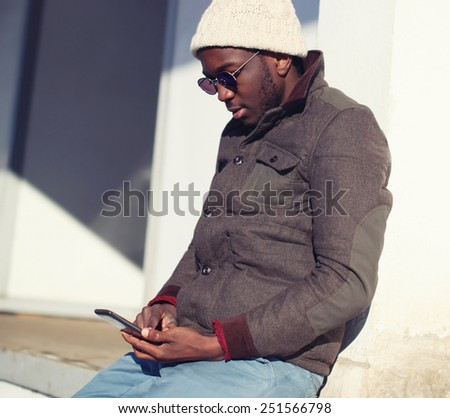 Lifestyle portrait of stylish young african man using smartphone in city - street fashion and technology concept - stock photo