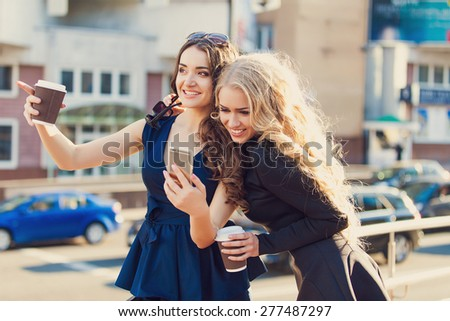 Lifestyle portrait of two best friends girls spending time in the center of the city at nice summer day, trendy fashion looks.
