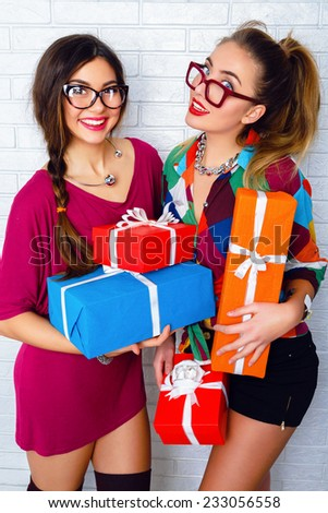 Lifestyle portrait of two pretty best friend girls holding a lot of bright birthday holiday presents, wearing sexy stylish trendy hipster party outfits and glasses. White urban wall background. - stock photo