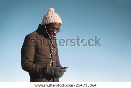 Lifestyle portrait of young african man enjoying listening music on smartphone against blue sky - stock photo