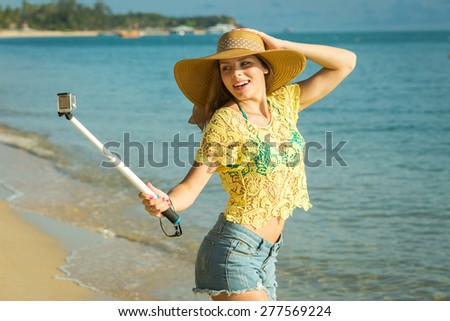 Lifestyle portrait of young lovely woman wearing a hat, a bright youth clothing, and making selfie with a stick against Samui beach. Having fun, joy and happiness. - stock photo