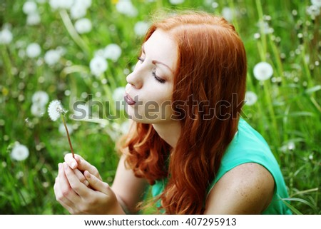 Lifestyle portrait of young spring fashion woman blowing dandelion in spring garden. Springtime. Allergic to pollen of flowers. Spring allergy