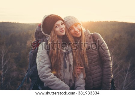 Lifestyle portrait of young traveler best friends girls at sunset, fun and smile  - stock photo