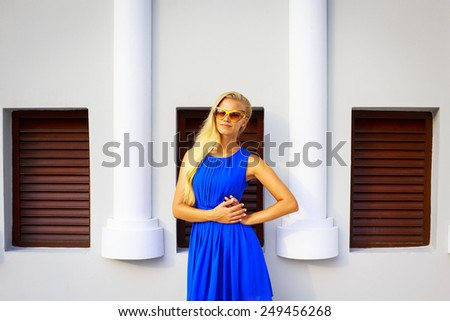 Lifestyle portrait of young woman in a blue dress and sunglasses. Sexy blonde woman posing in front of a wall.