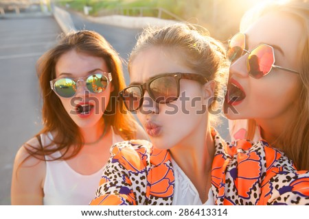 lifestyle self-portrait of tree best friends hipster girls wearing stylish bright outfits, denim shorts and glasses,going crazy and make funny faces,emotional people.Sunset background,urban city - stock photo