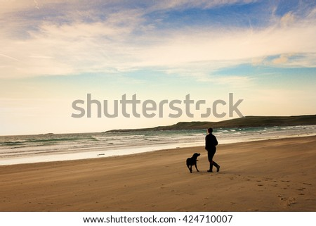 lifestyle shot of person with dog on beach