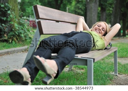 Lifestyle shot of young beautiful smiling woman lying on bench in park outside