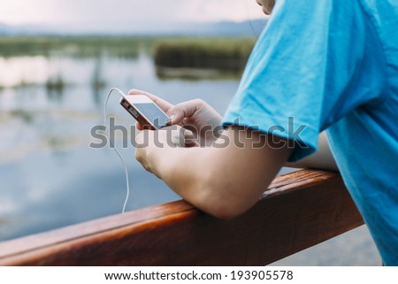 Lifestyle Smartphone Tech User Enjoying Vacation with retro filtered color effect - stock photo