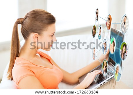 lifestyle, social networking and internet concept - woman using laptop at home - stock photo