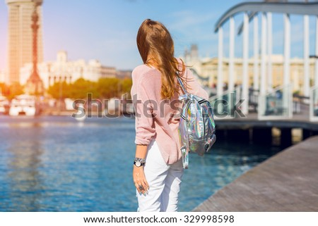 Lifestyle spring image of pretty girl posing back and arms overhead show sings , dreaming mood.  Blonde woman travels to Barcelona.Amazing view.  - stock photo