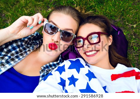 Lifestyle summer portrait of two best friends girls making selfie, looking on camera, flirting sending kiss and smiling, laying on the grass, wearing hipster plaid shirt, T-shirt with american flag. - stock photo