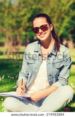 lifestyle, summer vacation, education and people concept - smiling young girl writing with pencil to notebook and sitting on grass in park