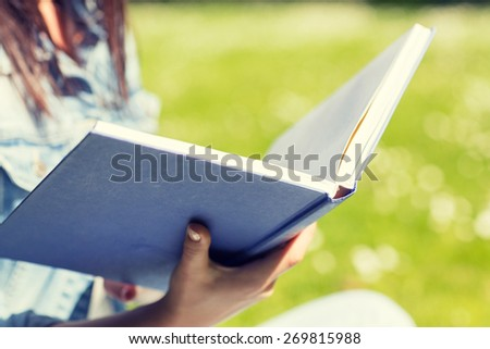lifestyle, summer vacation, education, literature and people concept - close up of young girl reading book and sitting on grass in park - stock photo