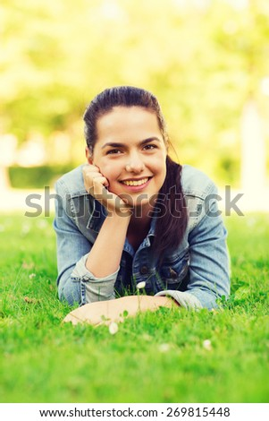 lifestyle, summer vacation, leisure and people concept - smiling young girl lying on grass in park - stock photo