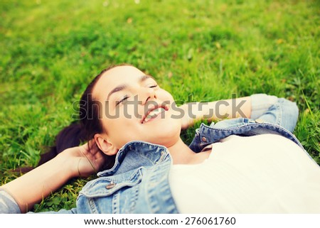 lifestyle, summer vacation, leisure and people concept - smiling young girl with closed eyes lying on grass - stock photo