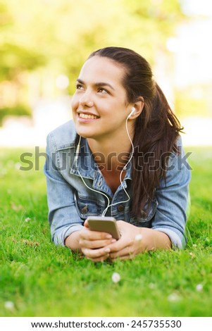 lifestyle, summer vacation, technology, leisure and people concept - smiling young girl with smartphone and earphones lying on grass - stock photo