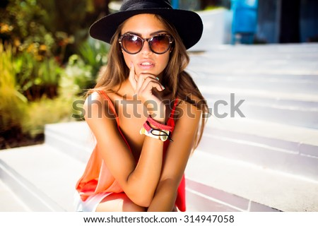 Lifestyle sunny fashion portrait of young stylish hipster woman walking on the street, wearing cute trendy outfit,wear trendy accessories and long black hat,smiling enjoy her weekends,travel,cute - stock photo