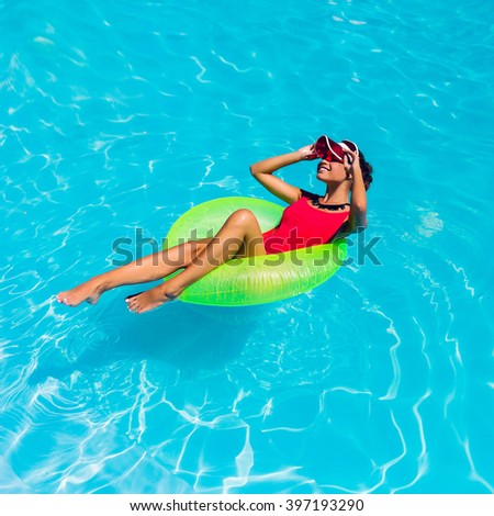 Lifestyle sunny image of young beautiful woman in stylish swimwear on rubber ring laughing , sunbathing, enjoying  holidays , vacation mood. Bright colors.  - stock photo