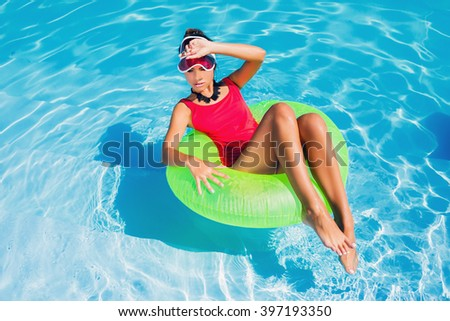 Lifestyle sunny image of young beautiful woman in stylish swimwear on rubber ring laughing , sunbathing, enjoying  holidays , vacation mood. Bright colors. Beach party.  - stock photo