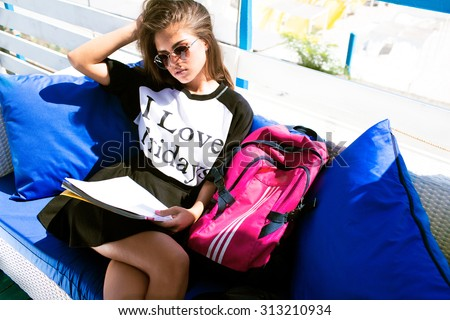 Lifestyle teen portrait of beautiful student girl,wearing printed sweater and skirt,autumn clothes and sunglasses.Soft autumn instagram color tone.Hipster girl,school uniform,school bag,papers - stock photo