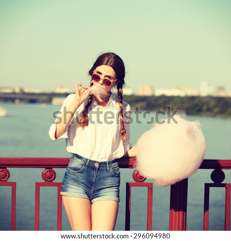 Lifestyle. Young happy hipster woman eating sweetened cotton candy, amazing view of the city from the bridge. Photo toned style Instagram filters. - stock photo