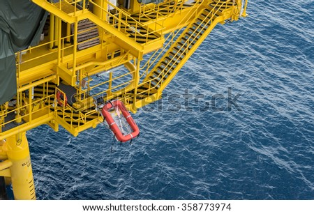 Lift raft installed at offshore oil production platform - stock photo