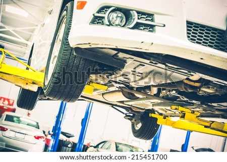 Lifted Car Maintenance. Servicing Car on the Car Lift. Auto Service Theme. - stock photo