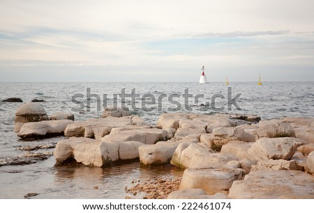 lighhouse in the background with rocks and calm see in foreground, istria, croatia - stock photo