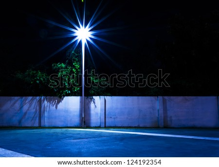 Light and Brick Wall on park at night time. - stock photo