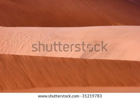 light and dark layers of red dunes - stock photo