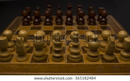 Light and dark wooden chess pieces on chess table. High resolution image.