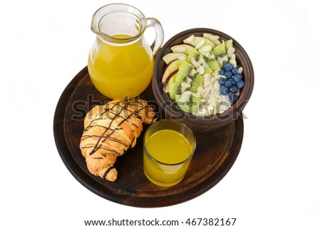Light and healthy breakfast: oatmeal with fruit and berries, orange juice, croissant. On a white background, isolation