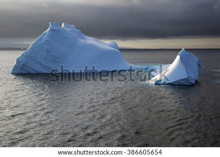 Light and shadow playing on an iceberg sculpted by wind and water in the Bransfield Strait (Antarctica) - stock photo