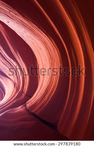 Light and shadows play over smoothly eroded sandstone walls with dynamic features and large cracks. - stock photo