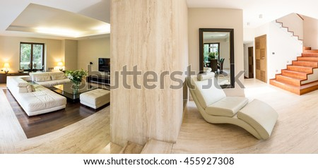 Light and spacious villa interior with expensive furniture and stairs, panorama