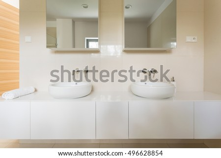 Light bathroom with white tiles, two basins and mirrors