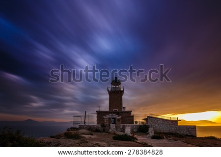 Light beacon and rocky wave breaker at sea in Greece against a blue sunset sky, long exposure photography - stock photo